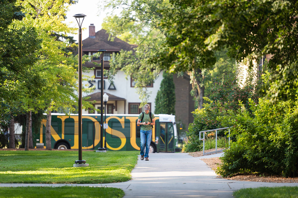 Students on campus with NDSU bus in background