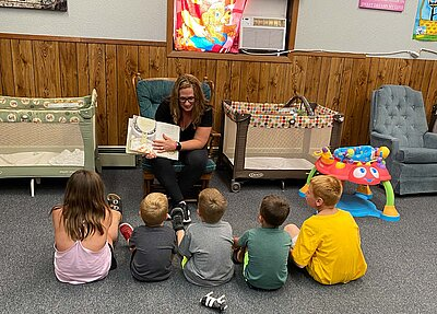N.D. 4-H alum Bridget Mattern reads to a group of young children
