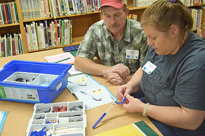 4-H volunteers work on a Lego Robotics project