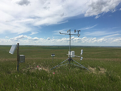 A remote weather station sitting in an open field.