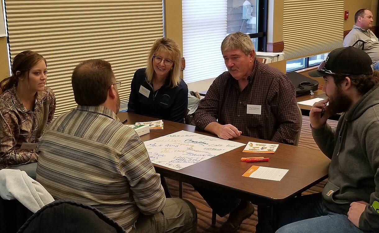 Five North Dakota Soil and Water Conservation Leadership Academy are gathered around a table discussing an issue.