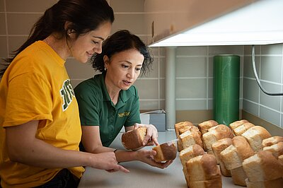Professor Senay Simsek and an NDSU graduate student examine loaves of bread