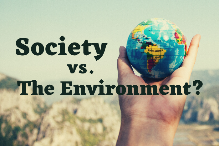 "A hand holding a globe with the words ""Society vs. the Environment?"""